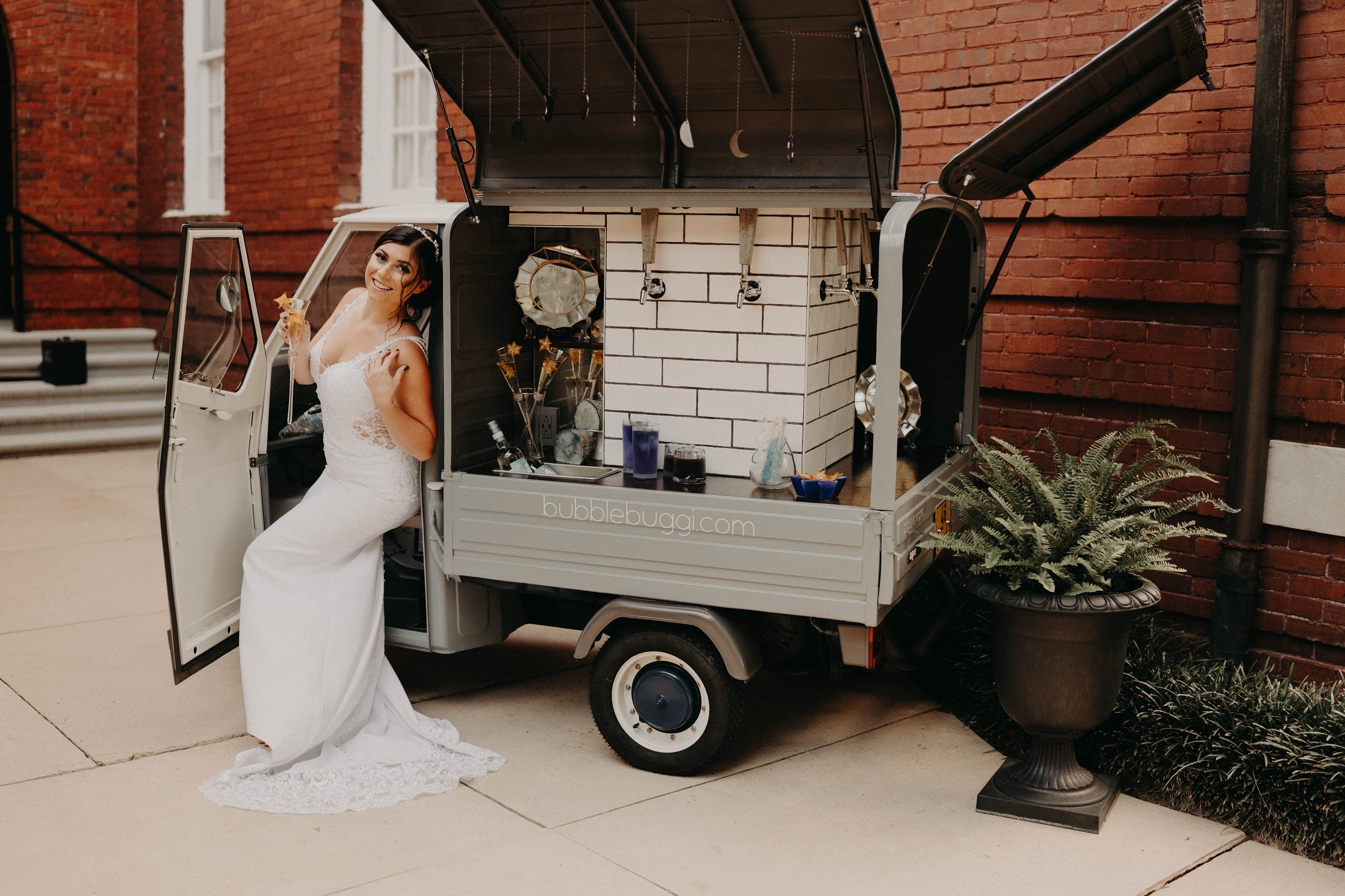 Vintage Italian Mini Truck converted into a tap truck with a bride sitting in the drivers seat.